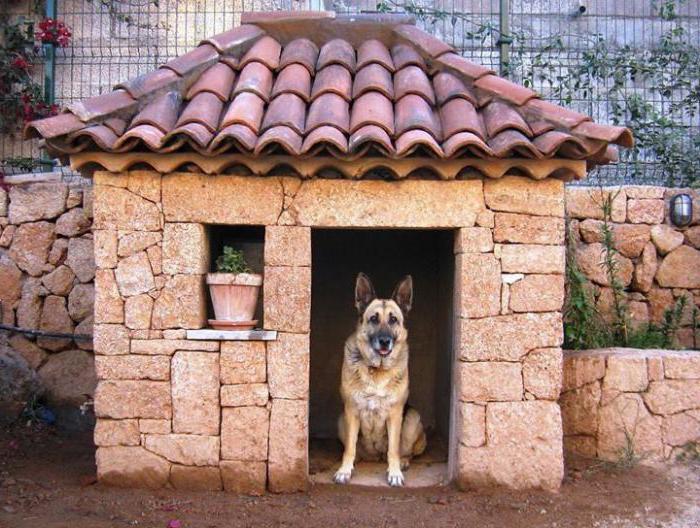 Взрослый пес в конуре, стилизованной под настоящий кирпичный дом с черепичной крышей